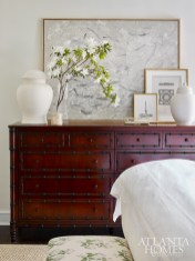 An abstract painting by McKenzie Dove represented by Pryor Fine Art rests on an English Colonial-inspired dresser from Williams- Sonoma Home.
