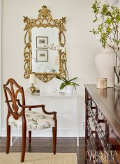An ornate mirror hanging above CB2's acrylic console showcases Lowe's knack for effortlessly combining design genres.