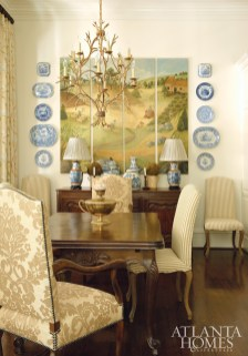 Flanked by a collection of blue-and-white porcelain, the custom four-panel farm scene was created by a Memphis-based artist for House of Hazen. The French dining table and chairs are from House of Hazen. opposite, top right The townhome's graceful architectural features are on display in the foyer, such as a transom window and a door painted Farrow & Ball's Pitch Black.