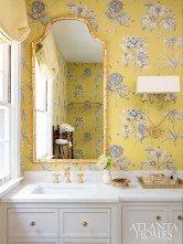 Brass hardware and a bamboo-style mirror accent the cheerful yellow wallcovering by Zoffany in the master bathroom.