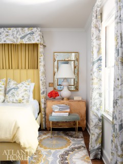 The patterned rug, draperies and bedding in the master bedroom coordinate with the wallcovering in the en suite bathroom.