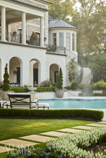 An arched opening on the loggia frames the pool, statue and wooded view on a single axis point, which is a hallmark of European design.