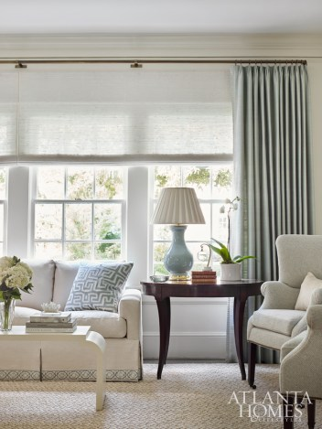 The tranquil color palette was inspired by the homeowner's affinity for duck-egg blue. In the living room, the soft hue was incorporated into the Samuel and Sons sofa tape. The sofa is by Mr. and Mrs. Howard for Sherrill Furniture; the rug is Fibreworks.