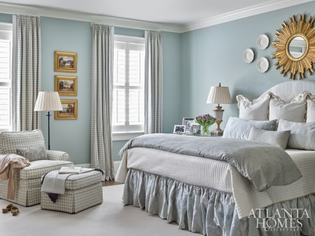The master bedroom also sings the blues, but accents of gold in the lamps, mirror and framed landscapes provide a comfortably luxurious look.
