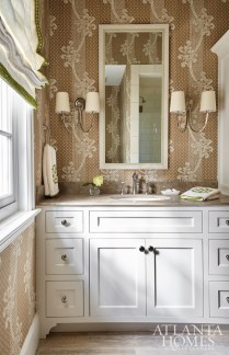 The adjoining bath, wallpapered in a khaki and white design by Sister Parish (Kinnicutt in brown) and a roman shade, also with green trim from Schumacher, keeps the palette flowing. The sconces are Visual Comfort and the towels are from Leontine Linens.