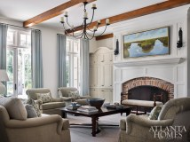 Designer Liz Williams infused the family room with quiet sophistication, employing neutral upholstery from Ferrell Mittman through Ainsworth-Noah and a fireside bench from Holland Macrae. A Rose Tarlow iron chandelier strikes a casual note; the Lowcountry landscape above the fireplace is by Charleston artist Laura Lloyd Fontaine.