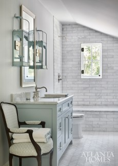 In a guest bath, the floor tile, set in a herringbone pattern, is from Renaissance Tile & Bath. The pale blue vanity is topped with a custom mirror from Caroline Budd's Picture Framing. The pagoda lanterns are from Lamplight Designs.