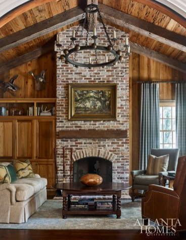 Pecky cypress, a hallmark of the coastal setting, gives the den a cozy feel. The room reads masculine thanks to tailored furnishings and fabrics, as well as from the hunting and fishing trophies, a passion of both father and sons.