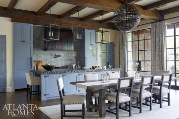 Created by stacking three slabs atop one another, a black absolute granite countertop with a chiseled top plays off of the clean custom kitchen cabinetry. One of several matching fixtures throughout the home, a spherical iron chandelier from Circa Lighting illuminates the long dining table from Four Hands and chairs by Lee Industries through Holland Macrae.