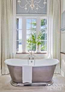 In the master bathroom, a patinated metal stool and a Waterworks bathtub with a metallic shell pop against the white marble flooring from Renaissance Tile & Bath.