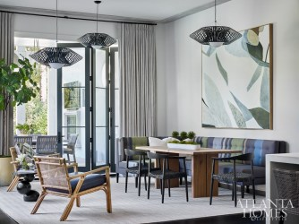 """In the breakfast area, a custom banquette by Bjork Studio features """"Big Stripe,"""" a fabric designed by fashion icon Paul Smith in collaboration with textile studio Maharam. Rattan chairs from Serena & Lily exude an organic, coastal feel. The light fixtures are by Possini Euro from Lightology and the art is by Vesela Baker."""