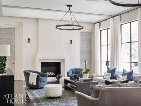 Designer Brian Watford filled the living room with seating from Bungalow Classic. To add architectural interest to the minimalist space, architect Yong Pak designed Art Deco-inspired door trims. The chandeliers are Restoration Hardware.