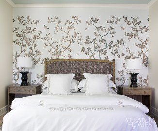 A cherry blossom wallpaper by Fromental through Holland & Sherry infuses natural beauty into a guest room. The lamps are John Boone.
