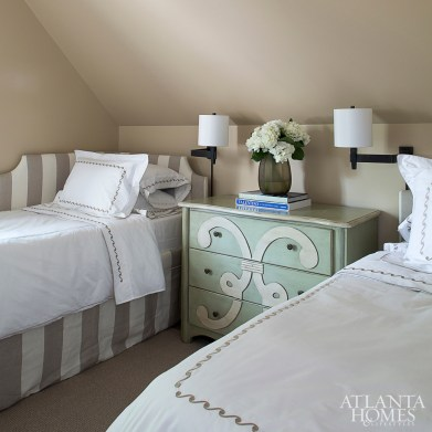 Part of the new addition above the garage, this guest suite features a pair of twin beds by Suzanne Kasler for Ballard Designs and bedding by Yves Delorme. The guest bathroom features sconces from Waterworks and a Cambria quartz vanity.