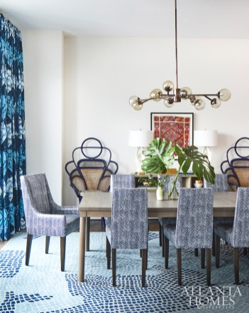 In the dining room of this Atlanta mid-rise, designer Andrew Howard incorporated treasures from the homeowner's travels, including a framed tapestry and vintage accent chairs. The dining chairs feature a Christopher Farr Cloth's fabric and are finished with a vinyl, a mindful touch given the client's dogs and grandchildren.