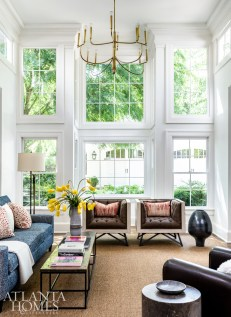 Sunlight streams into the family room, which is where everyone congregates, says Kleinhelter. A pair of tufted chairs upholstered in a Schumacher fabric anchor the space, which is balanced by a rustic coffee table and pair of vintage club chairs in a Kravet leather.