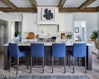 Barstools covered in midnight fabric from Arhaus and an abstract painting on the hood pack a punch in the kitchen, which received a modest makeover.