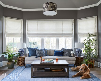 In the rear sunroom, the owner's well-behaved golden retriever, Toby, lounges next to the light sofa from Brice Ltd. The side tables are from World Market, and the lamps are from Wayfair.