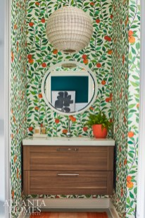 In the nursery bathroom, a vibrant wallcovering depicting oranges adds depth and dimension. The vanity is from IKEA.