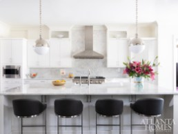 New marble countertops, pendants from Visual Comfort and a quartet of stools from Wayfair lend the kitchen an updated feel.