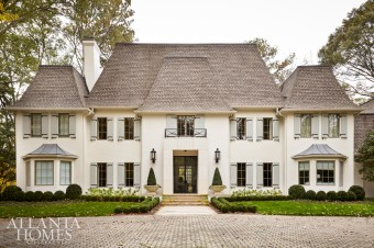 A mansard roof, charming wooden shutters and European-style gardens add instant character; the house was recently renovated by Amanda Orr Architects.