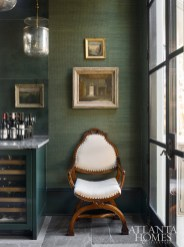 In one of the home's most dramatic changes, a former elevator shaft has been transformed into a luxe wet bar outfitted with a jute Phillip Jeffries wallcovering, an antiqued glass backsplash and Sable marble tile floors from Materials Marketing. An upholstered armchair from Robuck makes a handsome addition. The light fixtures are from Circa Lighting.