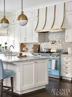 The kitchen, left intact from a recent renovation by Amanda Orr Architects for the previous homeowners, features a Lacanche stove, whose soft blue hue was the inspiration for fresh slipcovers for the barstools by Douglass Workroom.