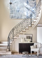 In the entry, designer Robert Brown introduced contemporary furniture and art as a counterpoint to the scrollwork stair railing, including the sleek Baker cabinet and a Natasha Baradaran chair. The architecture is by Harrison Design. The artwork is by Hutton Snellings.