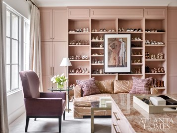 This hybrid dressing/sitting room highlights the wife's enviable shoe collection. The salmon hue of a Kelly Wearstler for Groundworks print on the sofa echoes the paint color of the cabinetry by Cardea Home.