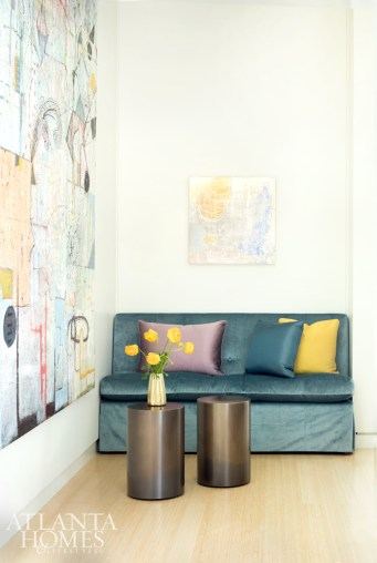 A velvet-covered armless love seat— designed by Suzanne Kasler Interiors and built by Bjork Studio—is energized by artwork by Mark Perlman (left) and Nancy Lorenz (center) in the foyer. The bronze tables are from Mathews Furniture.