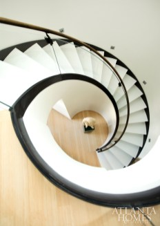 A spiral staircase with a glass railing leads to the second-floor bedrooms in the airy penthouse.