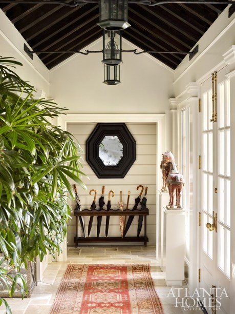 The hallway leading to a garage addition features a Chinese stone horse from The Nicholson Gallery and an octagonal mirror by Formations at Jerry Pair.