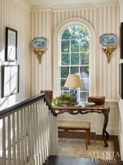 A custom stripe wallpaper by Cole & Son in the stair landing extends to the foyer, making for a classic entrance to this historical home.