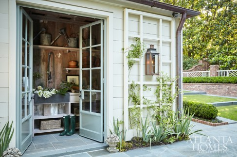 For the potting shed, architect William B. Litchfield drew inspiration from Bunny Mellon's whimsical greenhouse at Oak Spring Farm in Virginia. Vintage lumber lines the interior walls while exterior lattice screens allow for vines to frame this charming spot. Flowers by Holly Bryan.