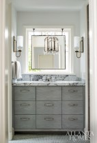 The husband has his own area of the master bath, including a vanity stained in a greige-colored finish. The custom mirror, fabricated by Brooks & Black Fine Framing, hangs in front of the window.