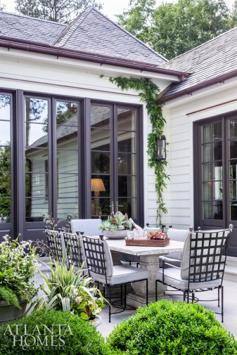 When the weather allows, the couple enjoys dining outdoors; the table and chairs are from Kolo Collection. Landscape architect Carson McElheney designed the home's lush grounds, which included both manicured and free-form plantings.