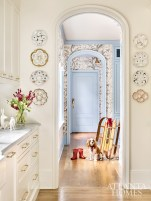 Amanda's antique oyster plates surround the arched entrance to the mudroom and her office, which sports a floral wallcovering and light blue-painted trim and cabinetry.