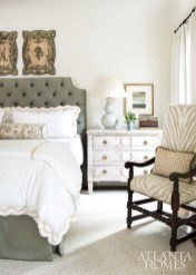 The master bedroom's tailored elegance springs from a custom headboard in a Schumacher wool, crisp Gramercy Home bed linens and French wall plaques from Foxglove Antiques & Galleries. The rug is by Stark.