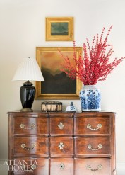 An antique chest in the living room is punctuated by a black lamp and Chinese porcelain filled with ilex berries.