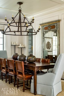Pieces with character, such as an antique Italian table and vintage leather chairs, define the dining space. The mirror is from Scott Antique Markets.