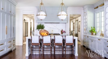 In the kitchen, cabinetry by Kingdom Woodworks was designed to resemble furniture as a nod to historic homes. The pendants are Visual Comfort.