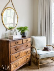 In the guest bedroom, an antique chest purchased in Belgium sits beside a chair from Selamat Designs covered in a playful fabric by Erika M. Powell Textiles.
