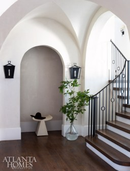In an alcove off the stairwell, cabinetry lays flush with the wall to hide two coat closets for convenient storage. The stool is by Made Goods.