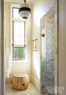 In the master bathroom, Roman shades by Schumacher are dressed with a velvet trim band, layering the space with warmth.