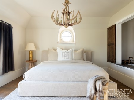 Located off the garage, the guest house is a rustic oasis filled with oatmeal tones, wood accents and an antler chandelier from the homeowner's personal collection.