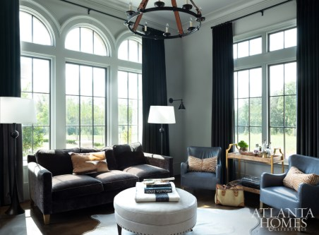 Charcoal gray sofas create a masculine presence in the husband's study—which frequently plays host to business calls and meetings. Warm tones in animal print pillows and a burled walnut and brass bar cart juxtapose the space's cool tones.