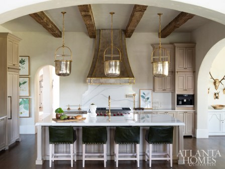In the kitchen, cabinetry—custom designed by Wright—is a smooth backdrop for shimmering light fixtures and stately stools. The metal hood was handcrafted on-site by builder Will Hines of Keeoco Development and then hand-finished to look like zinc. The pot filler is Waterstone.