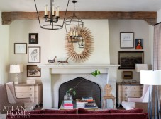 """Matching bleached pine chests from Bliss Studio rest on either side of a limestone fireplace, playing to the living room's symmetry. Antique oil paintings offer timeworn charm. """"I love for a house to look like it may have been around for 100 years, and then build on that,"""" says Johnson."""