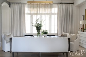 Draperies from Romo and a chandelier from Restoration Hardware contribute to the streamlined aesthetic of the dining room.