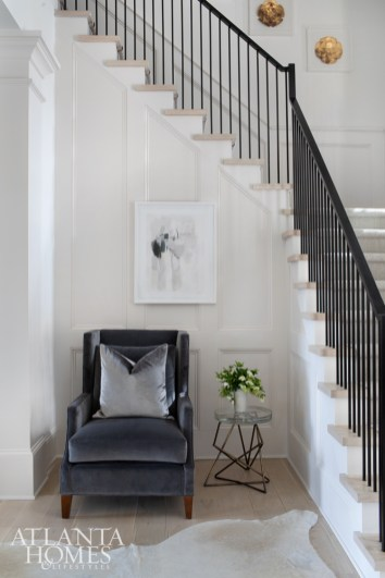 An iron banister and pllows and chair covered in Kravet velvet contrast with the white walls and white oak floors. The art is from Redefined Home Boutique and the John Liston architects stool is through R Hughes.